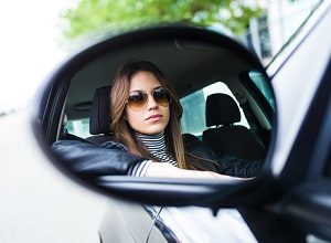 Woman in sunglasses driving car.
