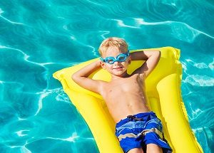 Young Boy Relaxing and Having Fun in Swimming Pool on Yellow Raf
