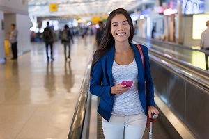 Travel woman using smartphone at airport.