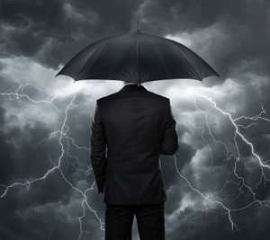 Suited man with umbrella behind a storm.