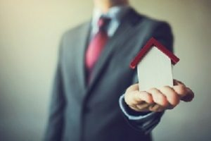 Business Man In Suit Having Miniature House On Palm Of His Hand
