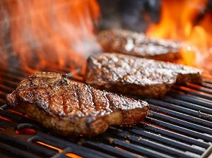 Grilling steaks on flaming grill.