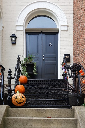 A front door that is black with 3 pumpkins on the stairs for Halloween