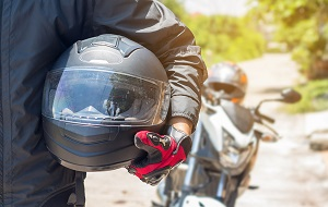 A man walking away from a motorcycle with a helmet in his arms