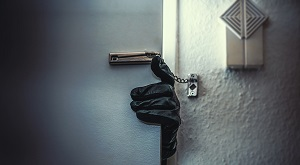 Burglar opening a door that has a chain lock on it