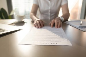 Businesswoman reviews lease agreement in office.