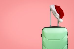Plastic Suitcase And Santa Claus Hat On Red Background.