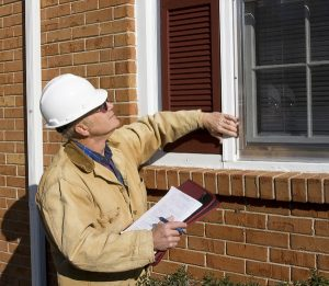A home inspector in a white hardhat inspects the exterior windows of a home.