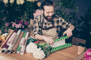 Man enjoying turning his hobby into a business and wrapping a flower bouquet in green paper
