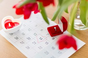 Calendar with Valentine's Day circled and diamond ring in gift box on top