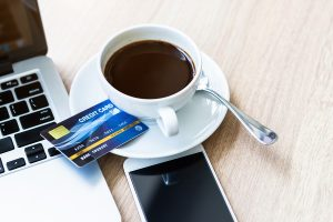 Laptop and cellphone Wi-Fi devices next to cup of coffee atop a credit card