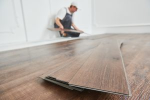 Worker doing renovations to his home by installing vinyl flooring