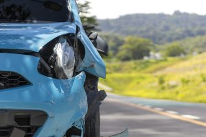 A damage blue car stranded on the side of the road after a hit-and-run accident