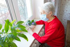 Elderly woman in mask pondering COVID-19's impact on life insurance while looking out window