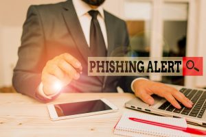 A business man using a laptop containing a COVID-19 email phishing scam.