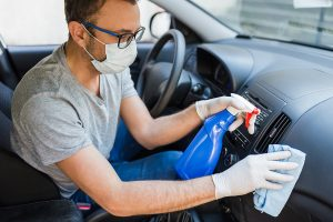 Man performing car maintenance and cleaning dashboard during quarantine.