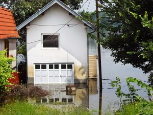 A house and garage situated near a lake that has been flooded, which is a common exclusion of homeowners insurance