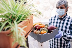 A male volunteer in a medical mask delivering a box of vegetables to someone's front doorstep