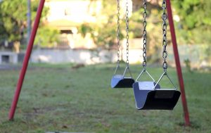 A swing set in a back yard, used to dedicate an attractive nuisance