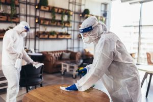 Two members of a professional sanitation crew clean the surfaces of a restaurant in hazmat suits after COVID-19 was discovered in the workplace.