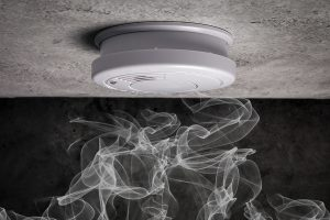 Smoke rising up to a smoke detector on the ceiling, stressing the importance of developing your family's fire escape plan