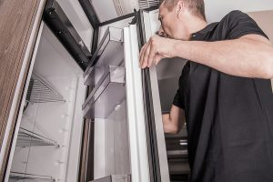 A man checking the door of a refrigerator to determine the cause of a leak