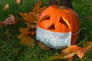 A Jack-o'-Lantern sitting atop green grass and yellow and orange leaves wearing a surgical mask of its mouth