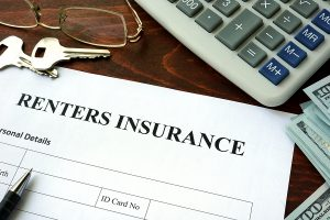 A close of the header of a renters insurance application on top of a desk next to a pair of keys, glasses, a pen, a calculator and one-hundred dollar bills.