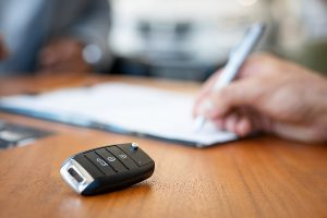 A closeup of an electronic car key on a desk with a hand holding a pen signing an extended car warranty in the background