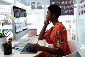 A side view of a female graphic designer working freelance on a computer