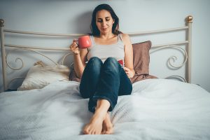 A single woman reading a booking in bed with a coffee mug in hand