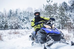 A man riding a snowmobile surrouded by pines