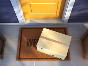 Online order package sitting on a welcome mat on a front porch in front of a yellow door and blue siding
