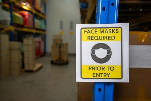 "A caution sign reading ""Face Masks Required Prior to Entry"" posting in a factory aisle"