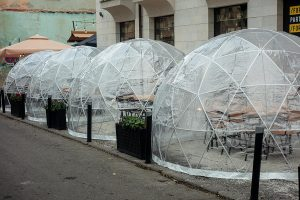 Plastic out door dining bubbles with tables and chairs inside to make for safe COVID-19 dining at restaurants