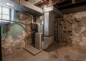 An old stone basement with a newly built furnace in the corner.