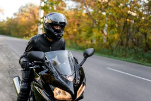 A young woman on a motocycle pulled over on to the side of the road wearing leather protective gear and a helmet.