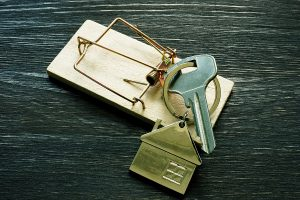 A pair of house keys in a mousetrap meant to represent rental and landlord fraud scams