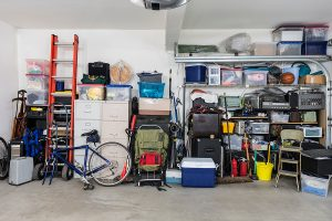 A cluttered garage with packed storage shelves, a bicycle, a ladder, and a load of other equipment.