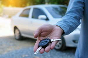 A man offering a pair of rental car keys with a white sedan in the background
