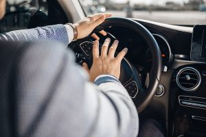 A man pressing his hand on the car horn of a steering wheel, meant to represent road rage.