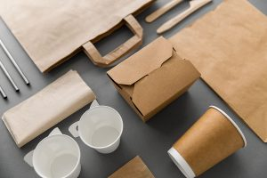 An assortment of biodegradable restaurant packaging including cups, straws, boxes, and bags.