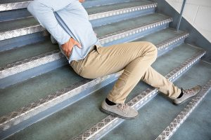 A man leaning on metal stairs and holding his lower back after taking a fall.