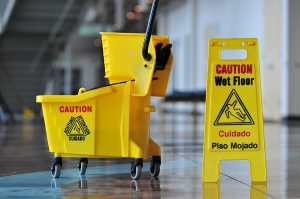 The inside of a store with a caution wet floor sign positioned next to a mop bucket.