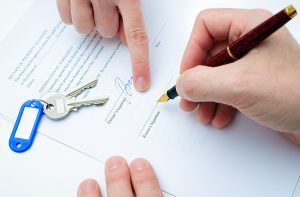 A person holding a pen about to sign a rental lease with a pair of key atop the agreement papers.