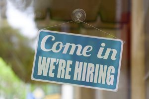 """Close-up On A Blue Sign In The Window Of A Restaurant Displaying The Words, """"Come in. We're Hiring."""""""