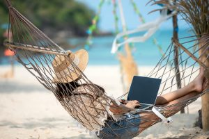 A woman laying in a hammock on a tropical beach on vacation using a laptop